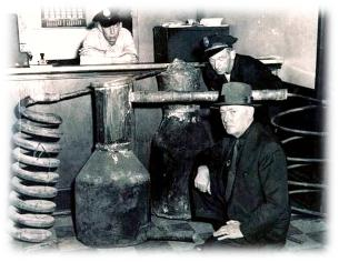 Image of an agent and police officers next to a siezed still.