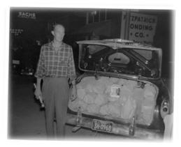 Image of an agent standing behind a car with the trunk open displaying bags of sugar.