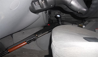 Image of same automobile interior front seat containing a how powered rifle