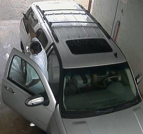 Image of a suspect standing outside of a white SUV while pointing a gun.