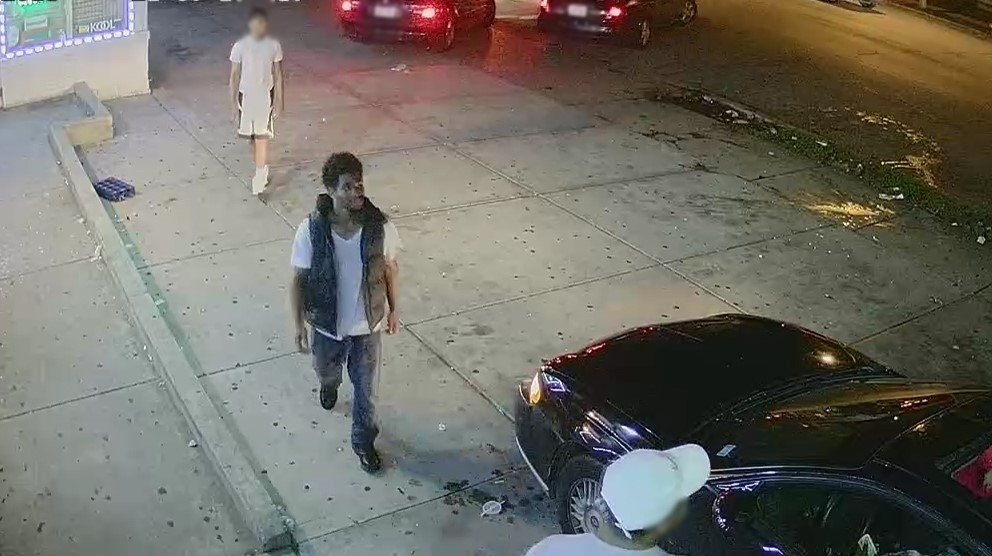 Image of a male suspect walking towards a black vehicle.