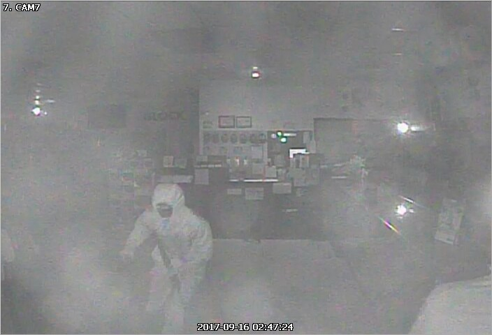 Person of interest seen wearing all white clothing in the midst of the robbery.