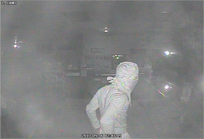 Second person of interest seen wearing all white clothing in the midst of the robbery.