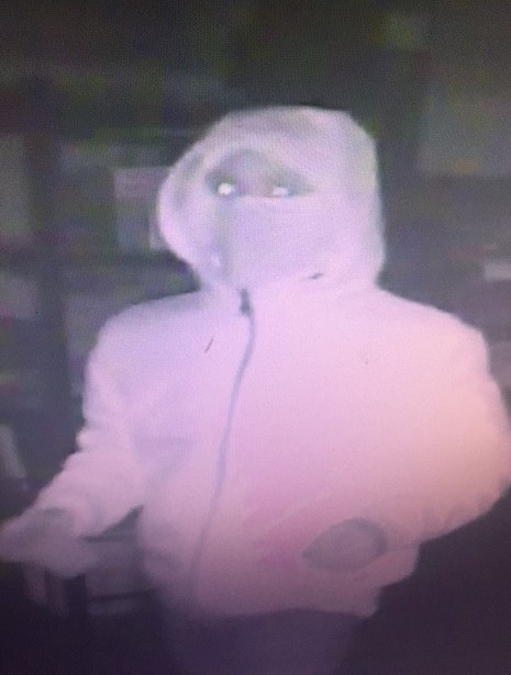 Image of suspect 2 with a light olored coat on and a scarf covering his face