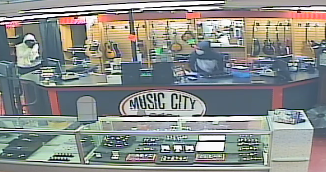 Image of two masked suspects actively robbing Music City Pawn