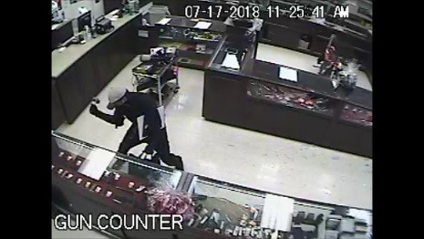Robbery suspect smashing display cases.