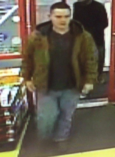 Image of suspect wearing a green military styled jacket, black t-shirt, blue jeans and black shoes.