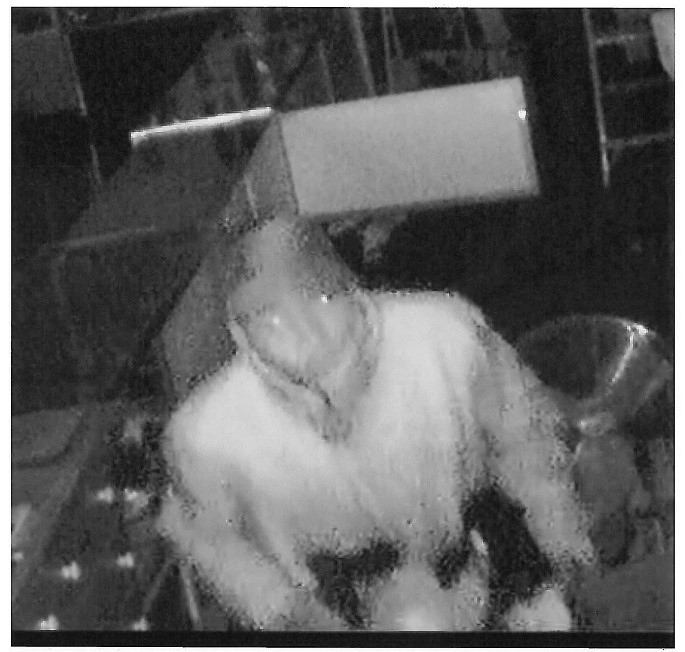 Image of a suspect wearing a dark hat and light clothing.