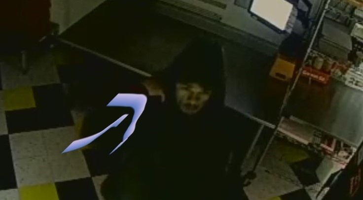 Unidentified male suspect in dark clothing with a hood over his head walking into Dublin Pawn Shop