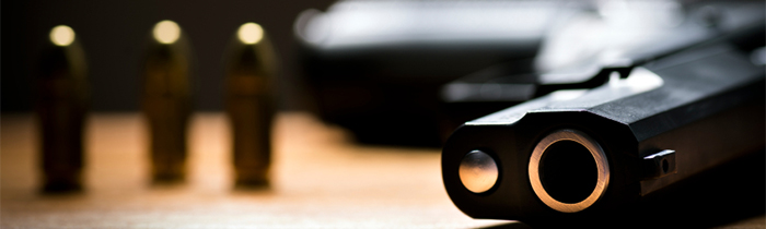 Image of a handgun and bullets on a table