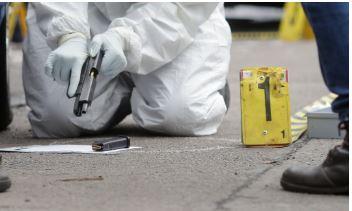 Un especialista forense recupera un arma de fuego y balas de una escena del crimen