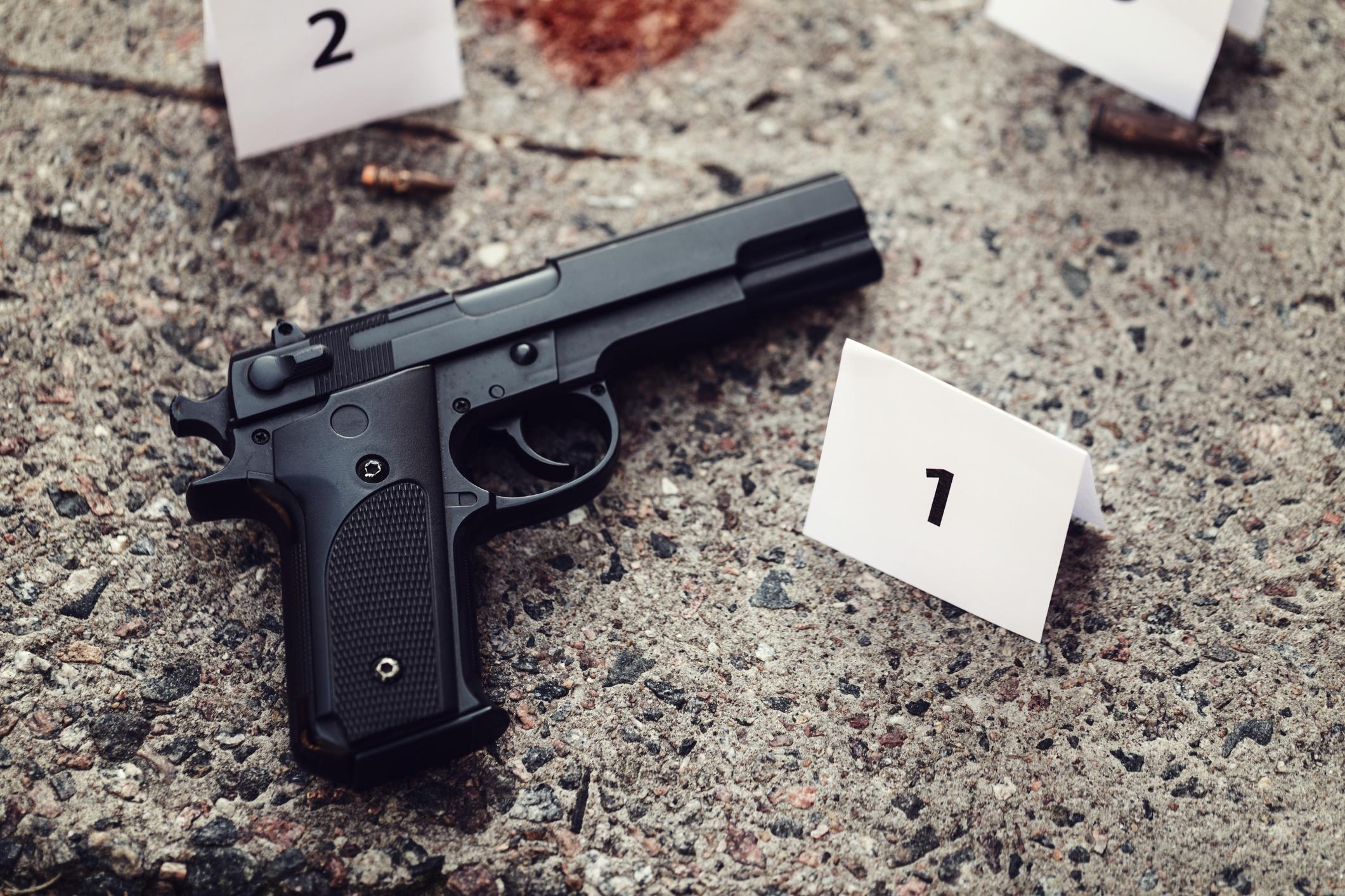 Pistola en un piso manchado de sangre junto a marcadores de evidencia.