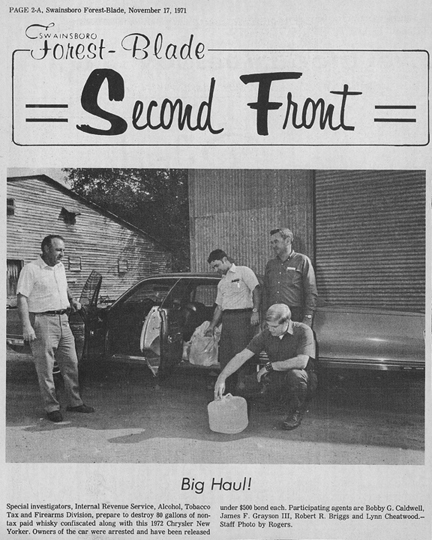 Swainsboro Forest-Blade page with image of Alcohol, Tobacco Tax and Firearms Division special investigators looking at a jug of confiscated non-tax whiskey.