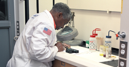 Scientist examines firearms and ballistic evidence